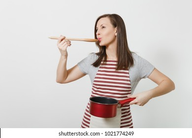 Young smiling caucasian housewife in striped apron, gray t-shirt isolated on white background. Beautiful housekeeper woman holding tasting red empty stewpan wooden spoon. Copy space for advertisement