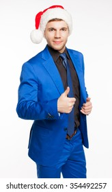 Young smiling caucasian male businessman in blue suit and santa hat showing thumbs up, on white background