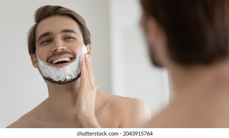 Young smiling Caucasian shirtless man applying shaving foam on face in front of mirror, preparing for hair removal morning routine. Concept of personal hygiene, skincare, male facial beauty products