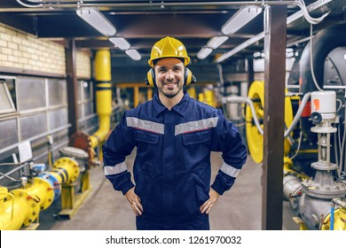 Young smiling Caucasian worker inn protective suit with hands on hips standing in heat plant.