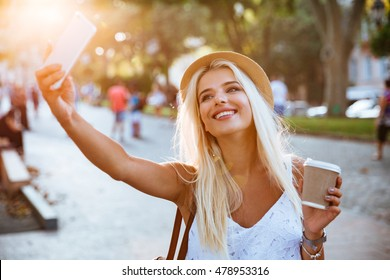 Young smiling cheerful blonde girl making selfie while standing on the street