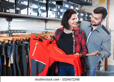 Young smiling cheerful positive couple choosing touristic trousers in sports clothes store