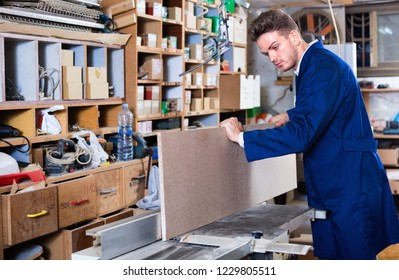 Young smiling cheerful positive guy fixing chipboard on table at workshop