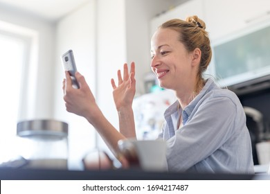 Young smiling cheerful woman indoors at home kitchen using social media on phone for video chatting and stying connected with her loved ones. Stay at home, social distancing lifestyle.
