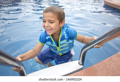 Young smiling child with life vest climbing from pool