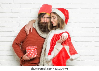 Young smiling Christmas or new year couple of bearded man with gift box and pretty sexy girl or beautiful woman in red santa claus costume with xmas bauble and sock on white brick wall