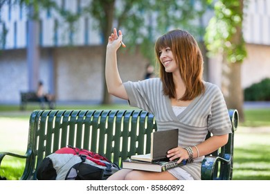 Young smiling college girl waving hand to person outside of image