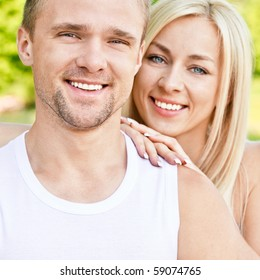 Young smiling couple against summer park.