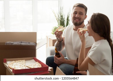 Young smiling couple eating pizza on housewarming party, celebrating moving day, man and woman beginning live together, sitting together on sofa, couch with unpacked cardboard boxes, first apartment