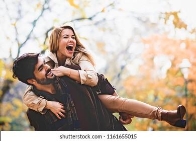 Junge lächelnde Paare, die Spaß im Park fallen.