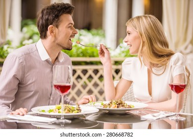 Young smiling couple enjoying the meal in gorgeous restaurant and drinking wine. Woman feeding man.