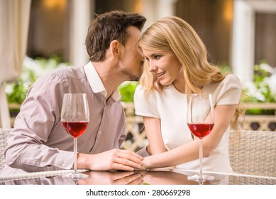 Young smiling couple enjoying the meal in gorgeous restaurant and drinking wine. Man whispering to woman.