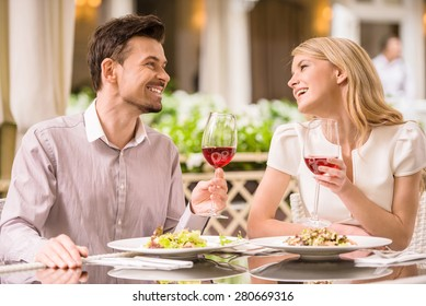 Young smiling couple enjoying the meal in gorgeous restaurant.