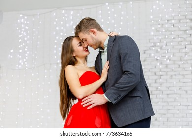 Young smiling couple in evening outfits (jacket and red dress). Harmony and happiness