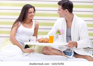 Young smiling couple having luxury breakfast in bed