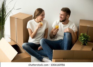Young smiling couple just moved into new home having break drinking juice packing unpacking cardboard boxes, happy man and woman ready to relocate sitting on the floor with belongings on moving day
