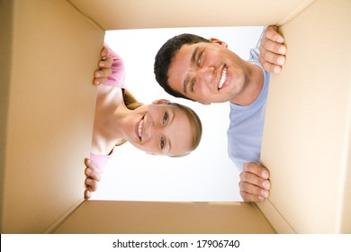 Young smiling couple looking into cardboard box. They're looking at camera. Low angle view.