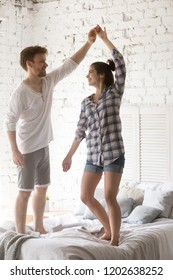Young smiling couple in love dancing at bed together in bedroom at home, husband holding attractive wife hand on date, spending time together, enjoying, just married man and woman in new apartment