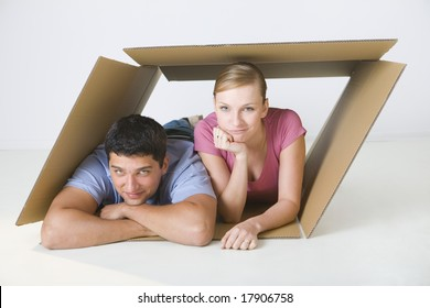 Young smiling couple lying in cardboard box. They're looking at camera. Front view.