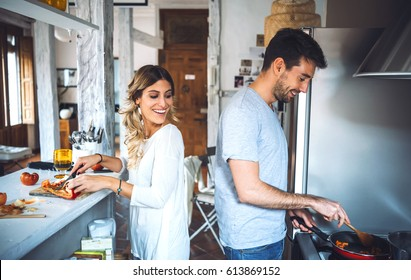 Young smiling couple preparing romantic dinner together at modern light kitchen.