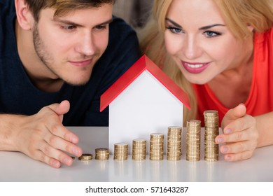Young Smiling Couple Protecting House Model With Stacked Coins On Desk. Real Estate Rent Growth Concept