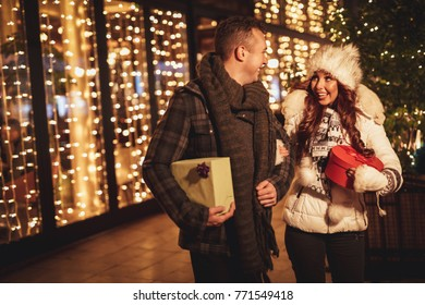 Young smiling couple in shopping passes in front of shopping mall. They are carrying gift boxes and having fun.