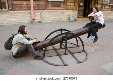 Young smiling couple sit on teeter-totter on street in summer