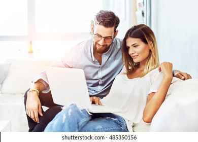 Young smiling couple sitting on the sofa and surf the Internet