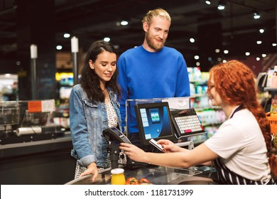 Young smiling couple standing near cashier desk happily paying for products by credit card in modern supermarket