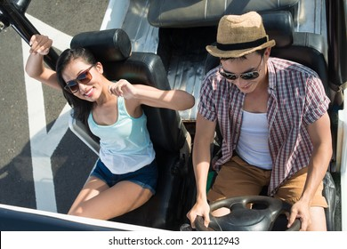 Young smiling couple in sunglasses travelling by off-road vehicle, view from above