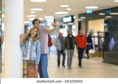 Young smiling couple take a selfie with their phone while shopping in the middle of a shopping center.