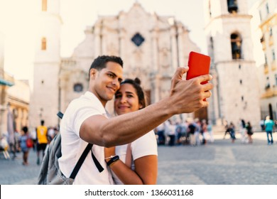 Young smiling couple taking selfie with smartphone in Havana, Cuba. Cathedral in the background.