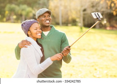Young smiling couple taking selfies on an autumns day