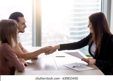 Young smiling couple visiting real estate agency shaking hands with realtor, purchasing renting flat or house, apartment buyers making deal, family couple and broker handshaking after signing papers