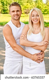 Young smiling couple in white clothes against summer park.
