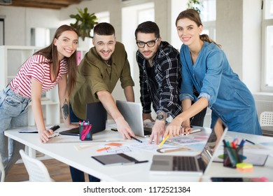 Young smiling creative people happily looking in camera working together with laptop. Group of cool guys working on new project spending time in modern office