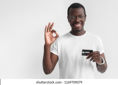 Young smiling dark skin african man in white t shirt holding credit card and showing okay sign isolated on gray background with copy space
