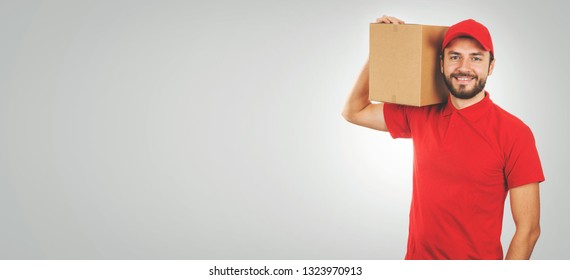 young smiling delivery man in red uniform and with shipment box on shoulder. copy space