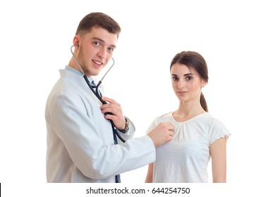young smiling doctor looks straight stands near girls and listens to her heart with a stethoscope