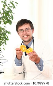 Young smiling doctor with orange in hands