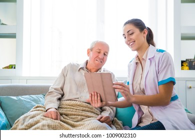The young smiling doctor sitting near the old, ill man and they looking at the tablet at home