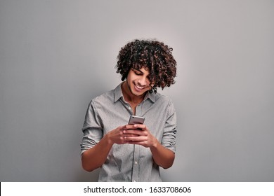 Young smiling eastern man looking at smarphone screen on isolated gray background. Joyful student using mobile phone