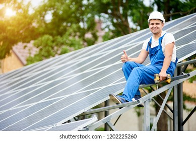 Young smiling electrician sitting on almost finished stand-alone solar photo voltaic panel system with screwdriver, showing thumb up gesture on bright sunny green tree background