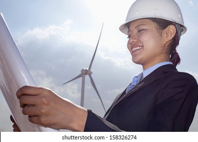 Young smiling engineer looking down at blueprints