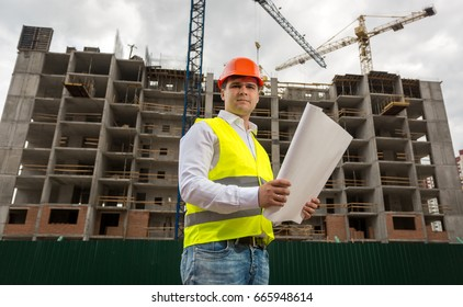 Young smiling engineer on building site checking plans and blueprints