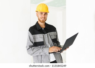 Young smiling engineer in work clothes and yellow hardhat joyfully looking in camera holding laptop in hand over white background