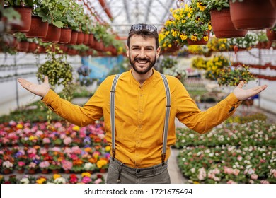 Young smiling entrepreneur standing in hothouse and presenting his flowers.