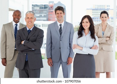 Young smiling executive standing in the middle of the room among his colleagues