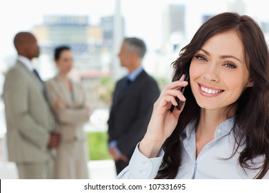Young smiling executive woman on the cell phone and tilting her head to one side