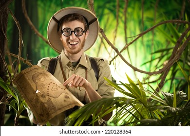 Young smiling explorer in the jungle with thick glasses holding a map.